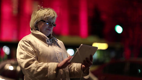 Businesswoman with glasses stands near the road and uses Tablet PC Footage
