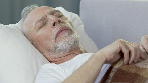Elderly man lying in bed, having troubled sleep, seeing nightmares, stressful Live Action