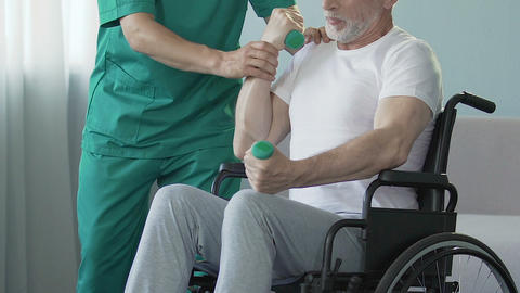 Senior man in wheelchair flexing arms with dumbbells, assisted by nurse, rehab Footage