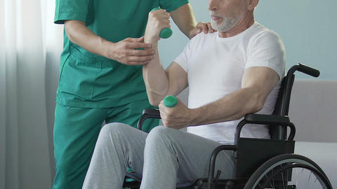 Elderly man in wheelchair lifting dumbbells, nurse by his side helping, trauma Live Action