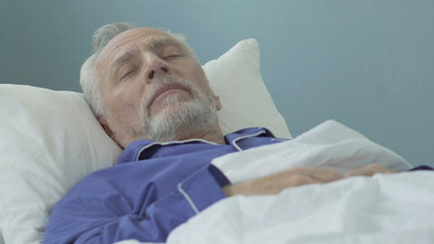 Senior man lying in bed and sleeping, healthy sound sleep, time in retirement Live Action