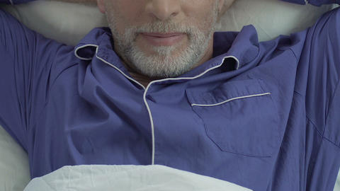 Aged male lying in bed and stretching, satisfied man waking up, close top view Footage