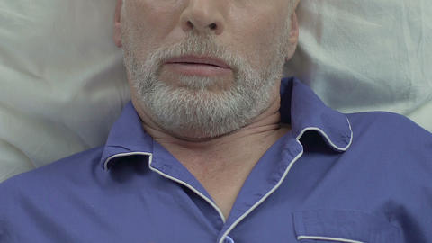 Bearded old male lying in bed and sleeping, snoring heavily, problems with sleep Footage