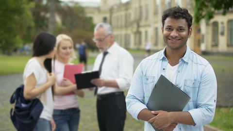 Happy Hispanic student standing near college and looking into camera, education Footage