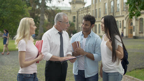 Professor giving assignments to group of multi-ethnic students, education Footage