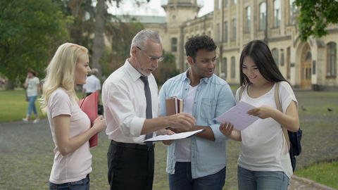 Male teacher giving tests to multi-ethnic students and explaining results Footage