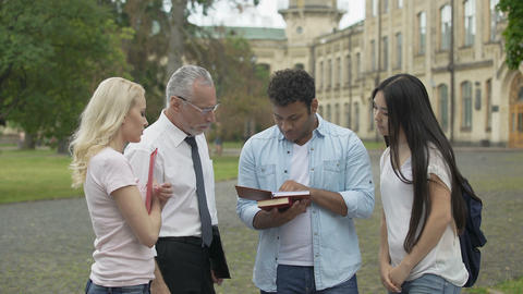 Senior geography teacher talking with students near college, explaining topic Footage