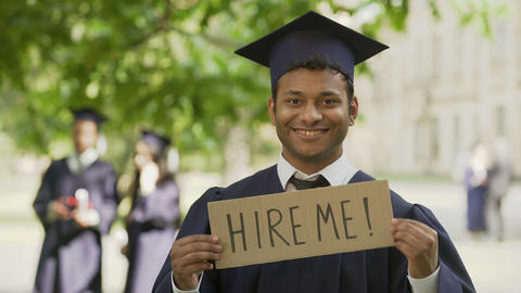 Young man in graduation gown holding table hire me, smiling, youth employment Footage