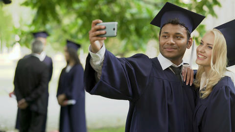 College friends in academic regalia taking photo with cellphone and checking it Footage