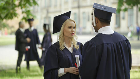 Female graduate in square hat with diploma talking to classmate, convocation day Footage
