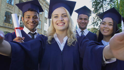 College graduates taking selfie on graduation day saying cheese, friendship Live Action