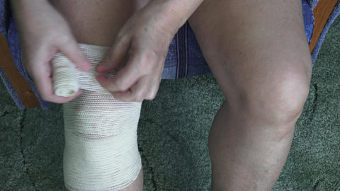 Bandaging the knee with an elastic bandage Footage