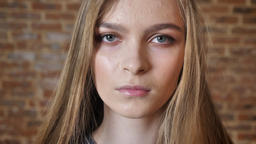 Face of young serious lady watching at camera, brick background, blurred Footage
