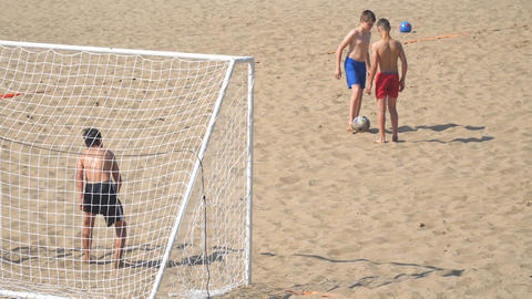 Boys teenagers playing soccer on the beach Footage