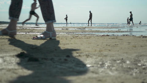 Silhouettes of diverse people and families on holiday on the beach in sunset Archivo