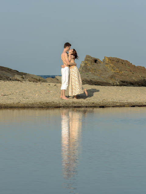 Boy and girl reflected in the lagoon between the mouth of the river and the sea Fotografía