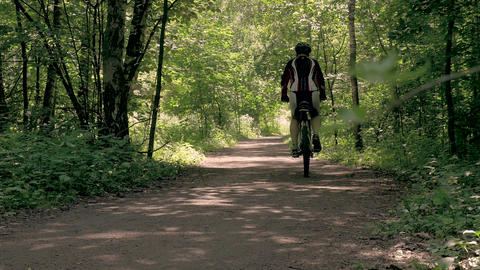 The athlete man drives through the forest on a bicycle. Healthy lifestyle Live Action