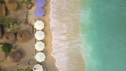 Aerial: Sandy Beach with Umbrellas and Lounge Beds at Paradise Tropical Island Footage