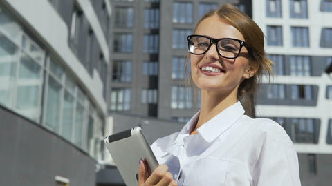 Businesswoman Holding Tablet in front of Corporation Live Action
