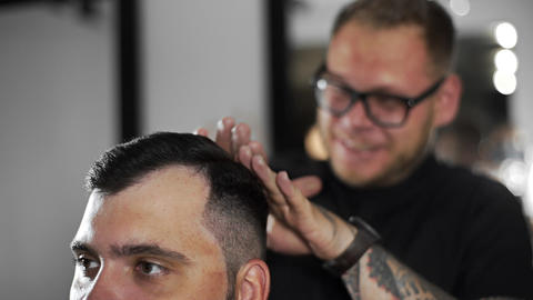 Tattoed barber makes hair styling with hair gel for customer after haircut at Footage