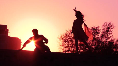 Happy couple dancing on beach enjoying honeymoon in nature at sunset silhouetted Footage