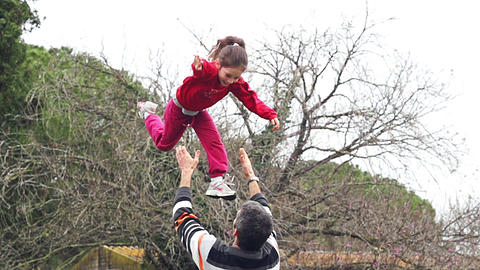 Slow motion of father throwing his adorable daughter in the air GIF
