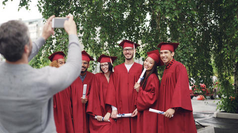 Proud father is taking pictures of graduating students with smartphone while Footage