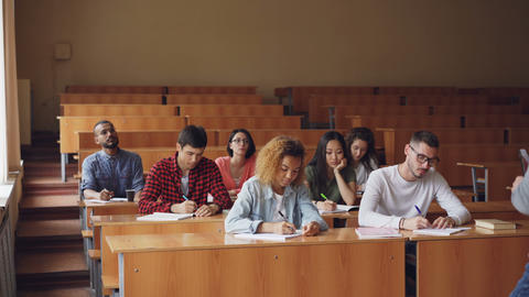 Professor is reading lecture to group of multiracial students standing in Live Action