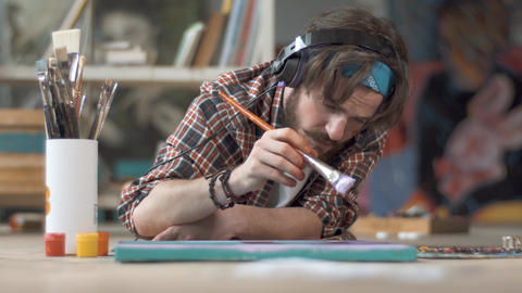 Artist Paints as Lying on Floor Archivo