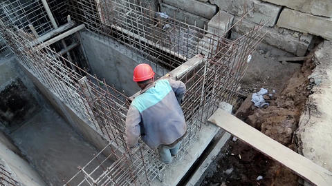 Builder with red hard hat at project site. Building of foundation Footage