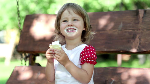 Cute little girl sits on the bench and eats ice cream Footage