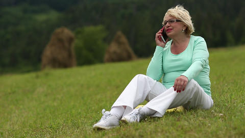 Woman with cell phone on the meadow Footage
