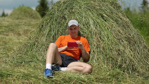 Man sits near haystack and looks through photos on his smartphone Footage