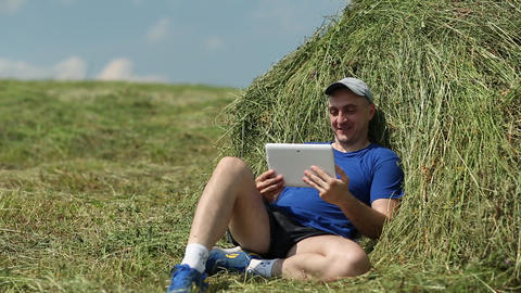 Man in dark blue t-shirt sits near haystack and communicates via tablet computer Footage