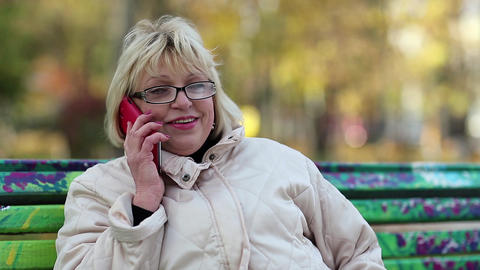 Woman sits on the bench and talks on the red smartphone Footage