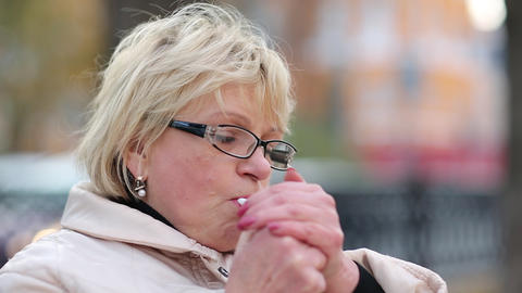 Senior woman sits on the bench near the road and smokes a cigarette Footage