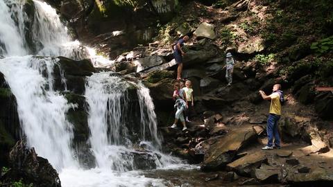 People near beautiful waterfall in Carpathian Mountains, Ukraine Footage