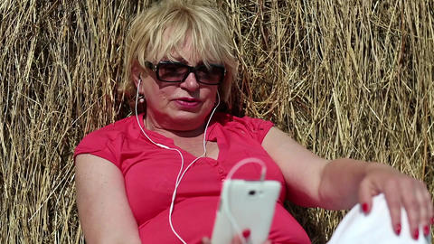 Woman sits near haystack and communicates via smartphone Footage