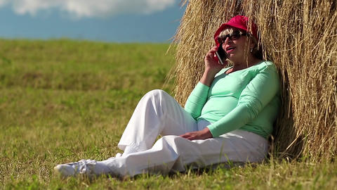 Senior woman sits near haystack and communicates via mobile phone Footage