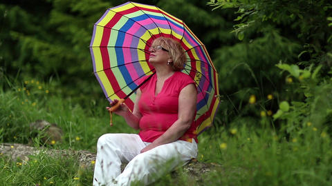 Senior woman with umbrella sits on a fallen tree in the forest Footage