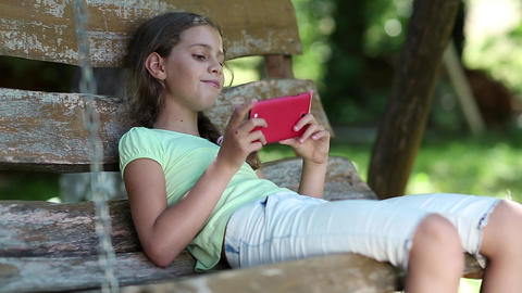 Girl with red smartphone sits on swing bench in the garden and listens to music Footage