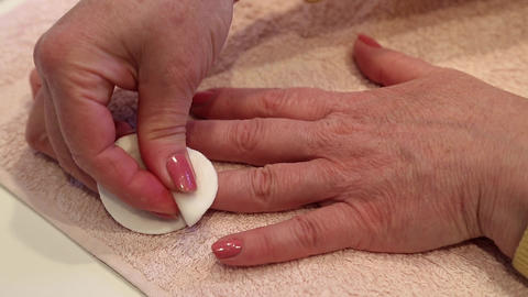Manicure treatment in beauty salon. Woman removes varnish from nail Footage
