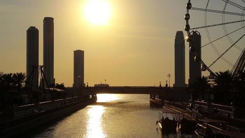 Al Qasba canal and ferris wheel in Sharjah city, United Arab Emirates. Sunset Footage