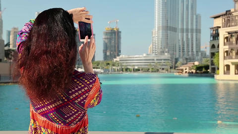 Pretty woman stands near the blue pool and makes photos on his smartphone Live Action
