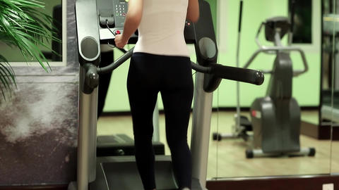 Woman trains in gym. Woman walking on the treadmill in the gym Footage