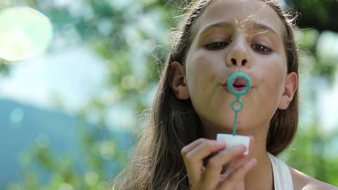Beautiful girl blowing soap bubbles Footage