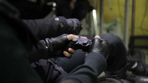 Male in leather gloves holding game controller playing video games, hobby Live Action