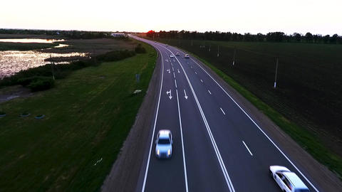 Highway traffic cars on the highway. Green wheat fields at sunset from a height Footage