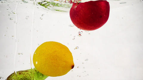 Whole lemon, apple and pear fall into a transparent container with water. Slow Footage