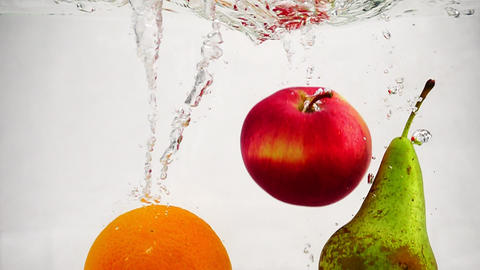 Slow motion video of pear, apple and orange falling into water with bubbles Footage